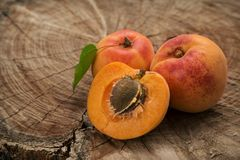 Three apricots, one is divided into half on a wooden background stock images