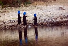 Three Arab women dressed completely in black taking water from the Nile River in Egypt. Near the city of Luxor Stock Photos