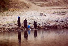 Three Arab women dressed completely in black taking water from the Nile River in Egypt, royalty free stock images