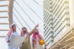 Three arabian engineer hold the blueprint and conference talking about the construction project with commitment to success in. Downtown with building background royalty free stock photo