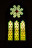 Three arch stained glass with black background. Vertical image of a beautiful stained glass church window with outdoor light gleaming through on a black Royalty Free Stock Photo