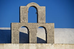 Three Arches Silhouetted Against Blue Sky. Three arches of a building in Santorini, Greece, are silhouetted against a blue sky Stock Photos