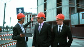 Three architects discuss newly constructed building. 4k. UltraHD. Three Young attractive businessmans architects in suits and helmet discuss about newly stock video footage