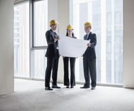 Three architects in hardhats examining a blueprint in an office building Royalty Free Stock Photo