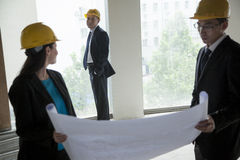Three architects in hardhats examining a blueprint in an office building Royalty Free Stock Photos