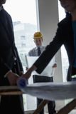 Three architects in hardhats examining blueprints in an office building Stock Photo