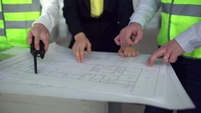Three architects look over plans together. 4 k close-up Architect working on project. Construction engineering concept