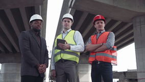 Three architects in protective helmets looking at camera. 4K movement stabilized shot of front view of three architects one african and two caucasians in stock video footage