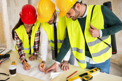 Three arhitects working together on construction site project Royalty Free Stock Images