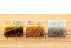 Three Aromatic Candles. Three cube-shaped aromatic candles on bamboo mat stock photo