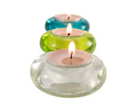 Three aromatic candles on white. Three aromatic candles in glass candlesticks for relaxation close-up Stock Photos