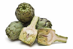 Three  artichokes and one cut. Royalty Free Stock Images