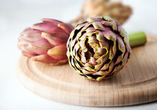 Three artichokes on a wooden cutting board.  Stock Photography