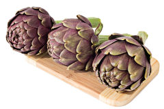 Three artichokes on a wooden plate Royalty Free Stock Images