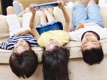 Three asian children using digital tablet together. Three asian children lying on couch at home playing video game using digital tablet royalty free stock photography
