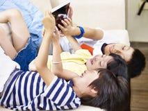 Three asian children using digital tablet together. Three asian children lying on couch at home playing video game using digital tablet royalty free stock images