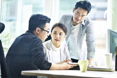 Three asian corporate executives meeting in office. Three young asian corporate executives meeting in office discussing business using digital tablet royalty free stock image