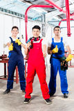 Three Asian industrial workers proud in factory Stock Images