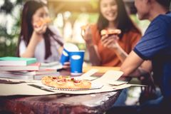 Three Asian people enjoy eating pizza at outdoors after tutoring. Class. Education and party concept. Food and Drinks theme. Happiness lifestyle theme royalty free stock photography