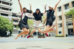 Three asian teenager jumping mid air with happiness emotion against school building background stock photo