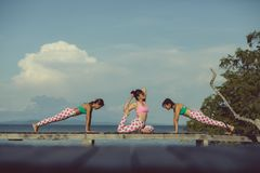 Three asian woman playing yoga flow on beach pier stock photography