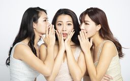 Three women telling whispering and secret gossip. Three asian women telling whispering and secret gossip royalty free stock image