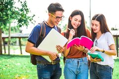 Three Asian young campus students enjoy tutoring and reading boo. Ks together. Friendship and Education concept. Campus school and university theme. Happiness Stock Photo