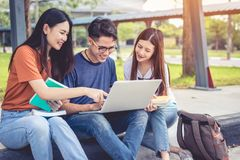 Three Asian young campus students enjoy tutoring and reading boo. Ks together. Friendship and Education concept. Campus school and university theme. Happiness Stock Photos