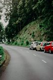 Three Assorted-color Vehicles Near Green Trees stock photo