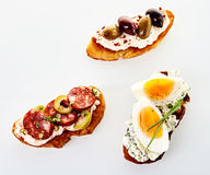 Three assorted fresh canapes on toasted baguette Stock Photos