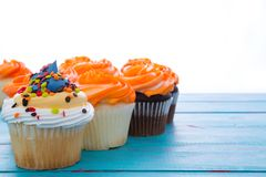 Three assorted iced cupcakes in a row Stock Image