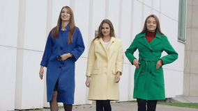 Three assured women walks runway in cashmere wool coats on the street. Slowly stock video footage