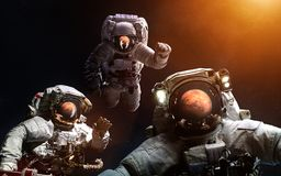 Three astronauts in front of Mars. Elements of the image are furnished by NASA. Three astronauts in front of Mars. Image in 5K resolution for desktop wallpaper Stock Photography