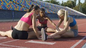 Three athlete girls sitting on sports field and stretching, workout and fitness stock video