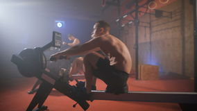 Three athletes doing rowing and air cycling crossfit exercises at the gym. Crossfit group training. Close up stock footage