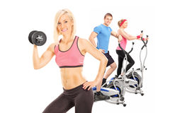 Three athletes exercising with fitness equipment Royalty Free Stock Photos