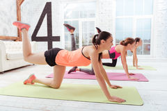 Three athletic women enjoying hard exercises in gym Stock Images