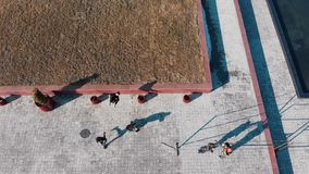 Three athletic young men overcoming obstacles and running from the grass on the road performing tricks. Aerial view stock video