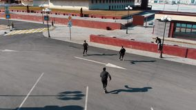 Three athletic young men running on the road and doing tricks. Aerial view stock video footage