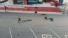 Three athletic young men running on the road and performing tricks. Aerial view stock video