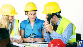 Three attractive engineers working with construction plans stock video