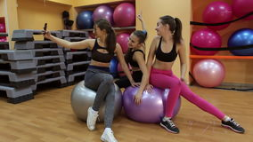 Three attractive girls are doing selfie in the gym. stock video