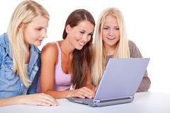 Three attractive girls using same laptop Royalty Free Stock Photo