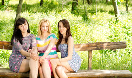 Three attractive girls on a wooden bench Stock Image