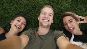 Three attractive millennial friends take selfies while lying on the green grass in the park or lawn. Caucasian man and stock footage