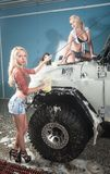 Three attractive sexy women washing car Stock Photos