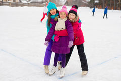 Three attractive skater girl hug on the ice Stock Photo