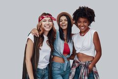 Three attractive stylish young women. Looking at camera and smiling while standing against grey background royalty free stock photo