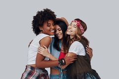 Three attractive stylish young women. Embracing and laughing while standing against grey background royalty free stock photos