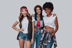 Three attractive stylish young women. Looking at camera and smiling while standing against grey background royalty free stock photos